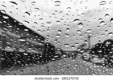 City view through a window with raindrops, rain in the city, Driving in rain, rainy weather. Water drops on glass surface, Road view through car window with rain drops,