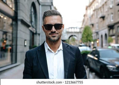 City walk. Man portrait. Handsome man is looking at camera and smiling; outdoors