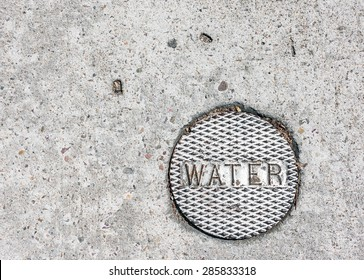 City water main cover embedded in rough pavement. Bumpy texture round metal plate with the word 'water'. Room for copy space.
