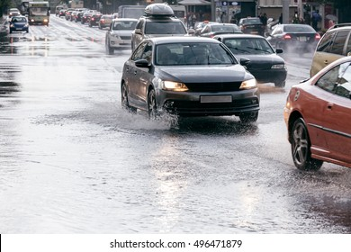 city wet road with puddles after downpour. cars driving on flooded road.