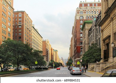 City: Wide Street with Traffic Island and Trees. School Zone with Brick Buildings in One-point Perspective.