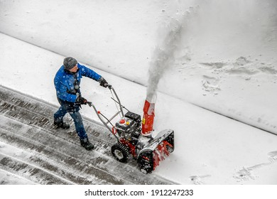 City worker clear snow with a snow thrower on the street during a snowfall in Kyiv, Ukraine, February 8, 2021.