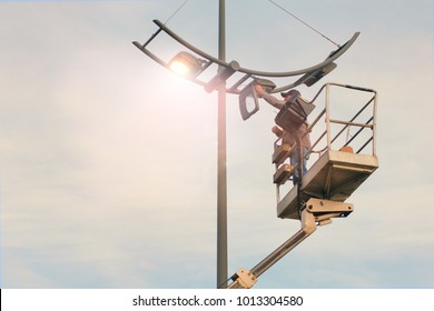 City Worker electrician installs a bulb into a street lamp. Profession that provides comfort, electricity in cities. Toned with warm retro filters.