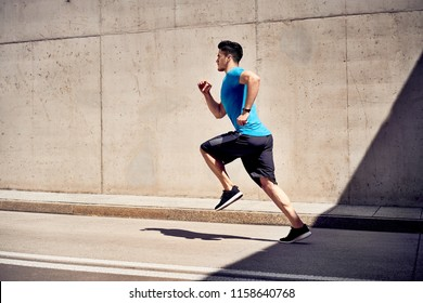 City workout concept. Athletic man doing running exercises on unused road