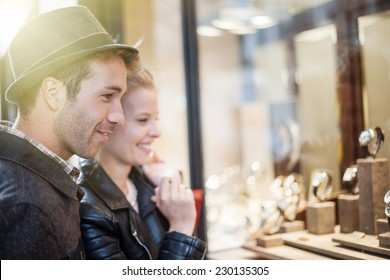 In the city a young trendy couple looking at watches in a showcase for woman's birthday