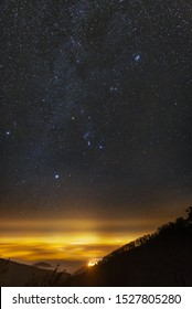 City of Zagreb light pollution illuminates the fog in the lowlands, while myn stars are visible in the winter night sky.