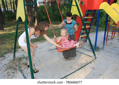 City of Zavodoukovsk, Tyumen Region, Russia, July 16, 2012: A girl with her mother and grandmother on the playground. Tour of the province.