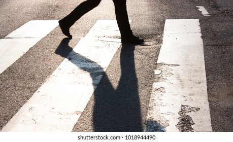 City zebra crossing with blurry walking pedestrian making long shadow in black and white high contrast