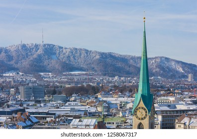 The city of Zurich in Switzerland as seen from the tower of the Grossmunster cathedral in winter, tower of the famous Fraumunster cathedral in the foreground, Mt. Uetliberg in the background.