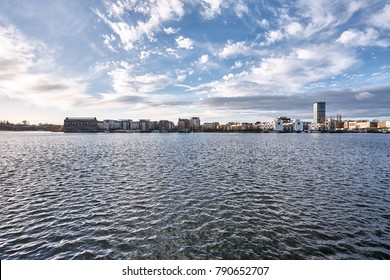 Cityscape across a lake under a blue cloudy sky on a mild winter morning
