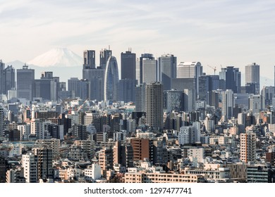 Cityscape aerial view of Shinjuku area with business buildings district and houses, Fuji mountain in background. Tokyo tourist attraction sightseeing, Japan travel landmark, or Asia tourism concept