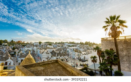 Cityscape of Alberobello; the trulli UNESCO world heritage town with unique stone walls, coned roofs, whitewashed housed during sunset evening, Puglia, Italy