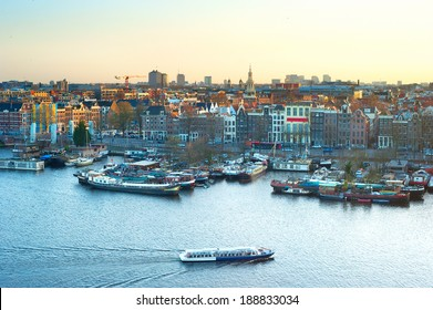 Cityscape of Amsterdam at colorful sunset. Aerial view