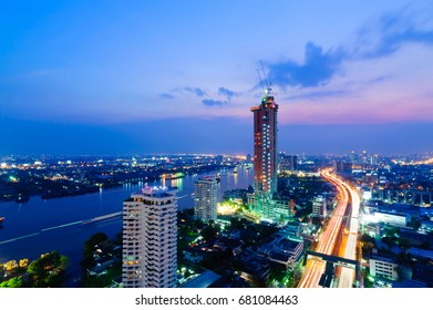 Cityscape of Bangkok's suburb in twilight with light trails in Chao Phaya river and street