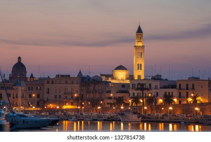 Cityscape of Bari at sunset with Basilica of San Nicola and Romanesque Cathedral. Bari, Puglia, Italy. seafront city view from marina at night. Apulia region