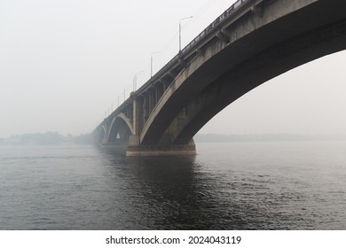 Cityscape with a Bridge Communal over the Yenisei river in Krasnoyarsk hidden in the heavy smog due to forest fires. Black sky mode in the city. Ecological catastrophe