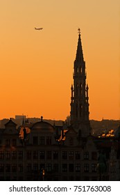 Cityscape of Brussels at sunset with city hall and aircraft flying above