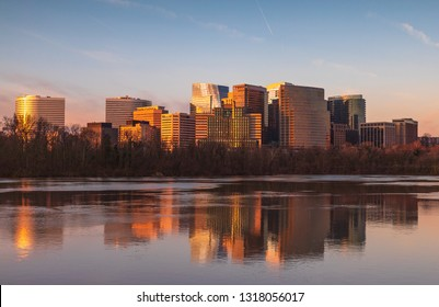 Cityscape of buildings in Arlington County, Virginia reflecting in the water of the Potomac River in morning light.