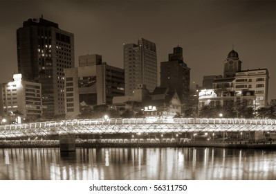 Cityscape of buildings in night with bridge over river.