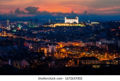 Cityscape with castle view over houses and bridge cathedral in Bratislava after sunset with lights