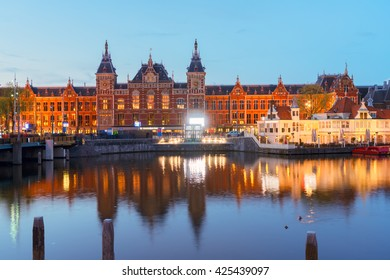 cityscape with central railway station and old town canal illuminated at night, Amsterdam, Holland