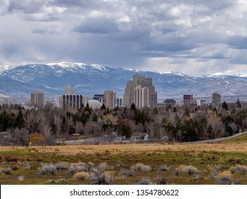 Cityscape of the City of Reno, Nevada as seen from the north with hotels, casinos, a park and snow capped mountains in the background.