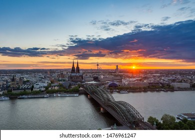Cityscape of Cologne and the river Rhine during sunset.
