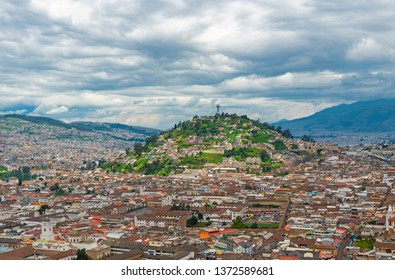 Cityscape of the colonial style architecture in the historic city center of Quito in a valley of the Andes mountain range with the Panecillo Hill and Virgin of Quito, Ecuador, South America.