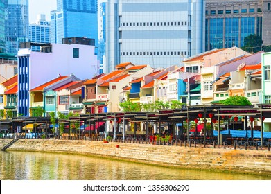 Cityscape with colorful bars, restaurants and stores by the Singapore River along Boat Quay, skyscrapers of modern architecture in background