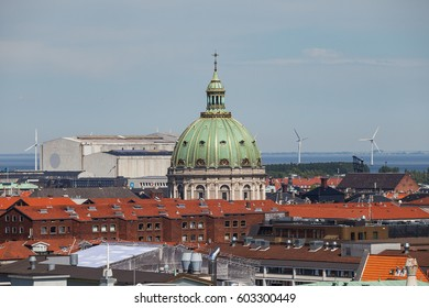 Cityscape of Copenhagen from the Round Tower. Dome of Frederik's church and wind turbines on the background
