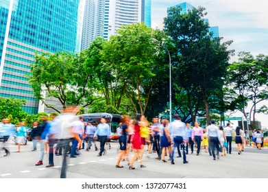 Cityscape with crowd of business people crossing road in Singapore downtown, metropolis skyline in background