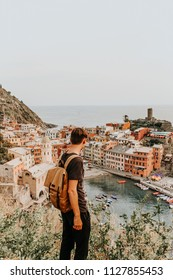 Cityscape in Europe, Cinque Terre, Italy. Mountains on the shores of the Mediterranean Sea. Young man enjoys the view. Vintage Modern colors. Background for the inscription. A popular place to travel.