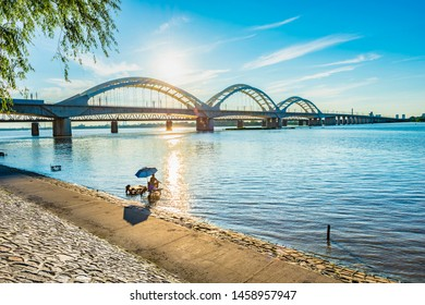 Cityscape of Harbin. Harbin Songhua River Railway Bridge. A man is fishing by the riverside. Located in Harbin, Heilongjiang, China.