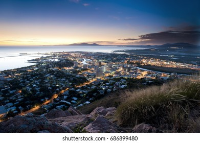 Cityscape of illuminated Townsville and ocean at dusk, Australia