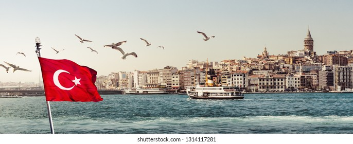 Cityscape of Istanbul on sunrise. Steamboats with a Turkish flag and flying seagulls over the Golden Horn. Panorama of the old town near Galata tower in Beyoglu, view on landing stage of Karakoy.