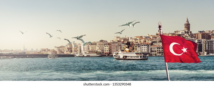 Cityscape of Istanbul on sunset - steamboat with red Turkish flag and flying seagulls over the Golden Horn. Panorama of the old town near Galata tower in Beyoglu, view on landing stage of Karakoy.