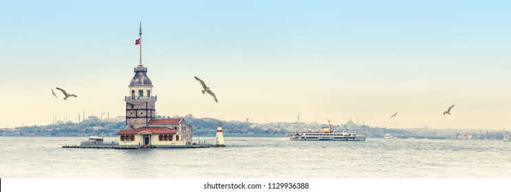 Cityscape of Istanbul with passenger ships and Maiden's Tower, wide angle shot for your billboard. Panorama of Bosporus Strait with Kiz Kulesi Tower, seagulls and silhouettes of mosques at skyline.