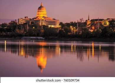 Cityscape of the Jefferson City skyline with the Missouri State Capitol reflecting in the river at twilight.