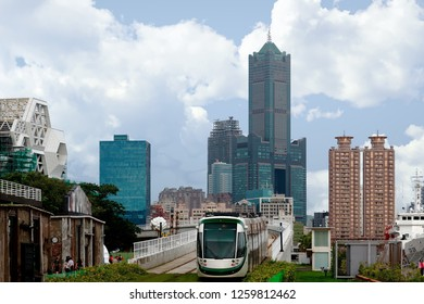 Cityscape of Kaohsiung, a vibrant metropolis in Southern Taiwan, with 85 Sky Tower standing among skyscrapers in background & a metro train traveling on a light rail overpass by the Pier-2 Art Center