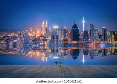 Cityscape of Kuala lumpur city skyline wooden walkway at night in Malaysia.