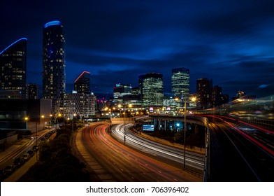 Cityscape of London at night in Canary Wharf, The city's second largest financial center, with light trails on the freeway leading to the modern skyscrapers of this district, a landmark of England, UK