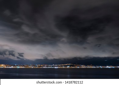 Cityscape at night. Big city lights at a cloudy night. City, sea and cloudy sky.