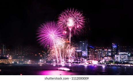 Cityscape of night skyline Pattaya City and Colorful fireworks. Celebration and anniversary concept. Pattaya International Fireworks Festival 2018 at Pattaya beach  on twilight background, Thailand.