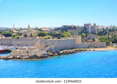 Cityscape of old town Rhodes: palace of grand knights, clock tower, mosque in Rhodes, Dodecanese, Greece