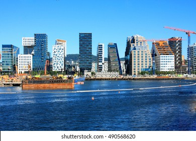 Cityscape of Oslo city with large buildings and sea water in a summer day.