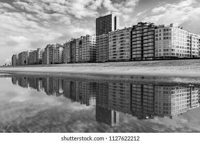The cityscape of Ostend in black and white with its urban skyline reflection in the North Sea and waterfront, West Flanders, Belgium.