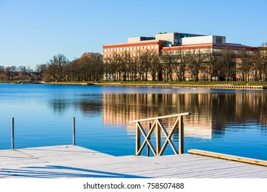 Cityscape over the Vaxjo lake in Sweden one fall morning. Lake is motionless and calm with alleyway and hospital building in background. Frost on the pier in the foreground.