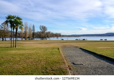 cityscape with palms and lawn at public park of touristic historical village on shore of Verbano lake, shot in bright winter light at Angera, Verbano, Varese, Lombardy, Italy