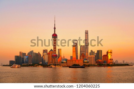 Cityscape and panorama of modern architecture,  warm colors and sunset on river of shanghai pudong skyline and skyscrapers, China