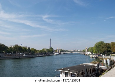 Cityscape of Paris, France. River Seine crossed by Pont Alexandre III (Alexandre 3rd Bridge). Eiffel Tower, blue skies and blue water on sunny day. Gold statues on bridge. Houseboats in foreground